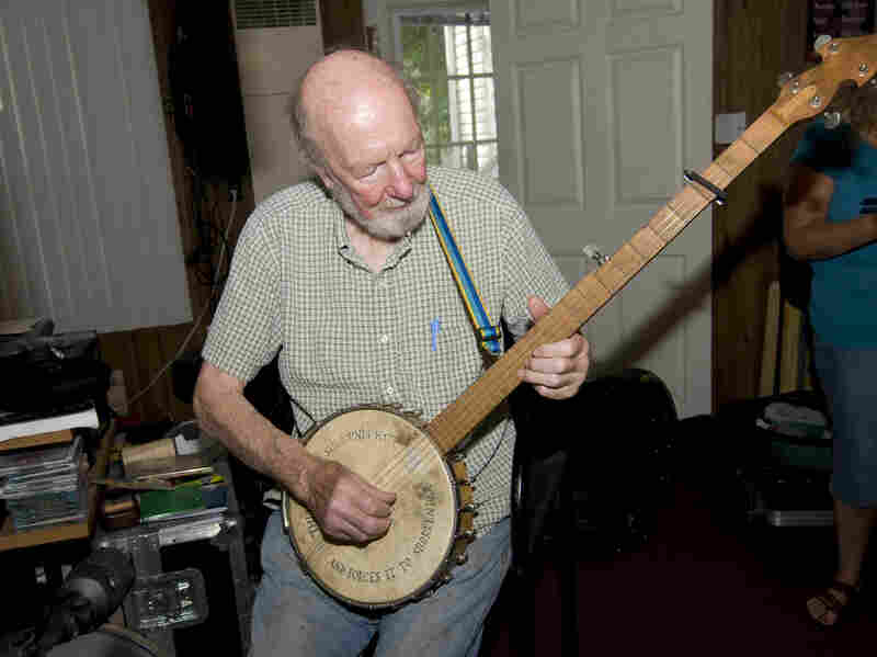 """Seeger shows off his banjo, inscribed with the message, """"This machine surrounds hate and forces it to surrender."""""""