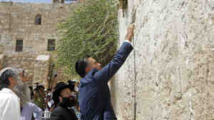 Republican presidential candidate Mitt Romney places a prayer note during a visit to the Western Wall in Jeru