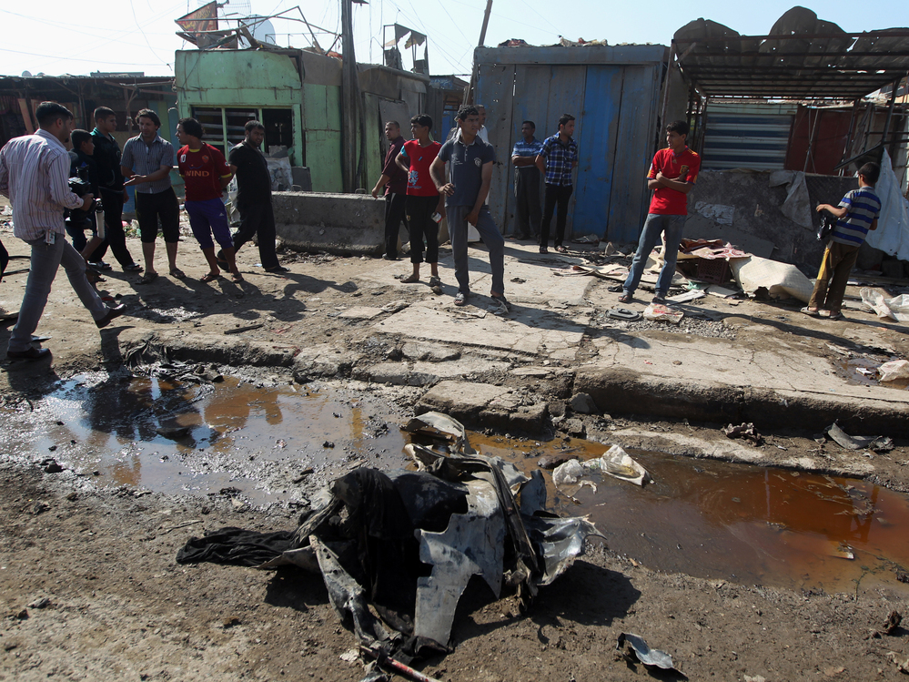 Iraqis inspect the site of a bombing at Al-Bawia market, in east Baghdad, on Saturday.
