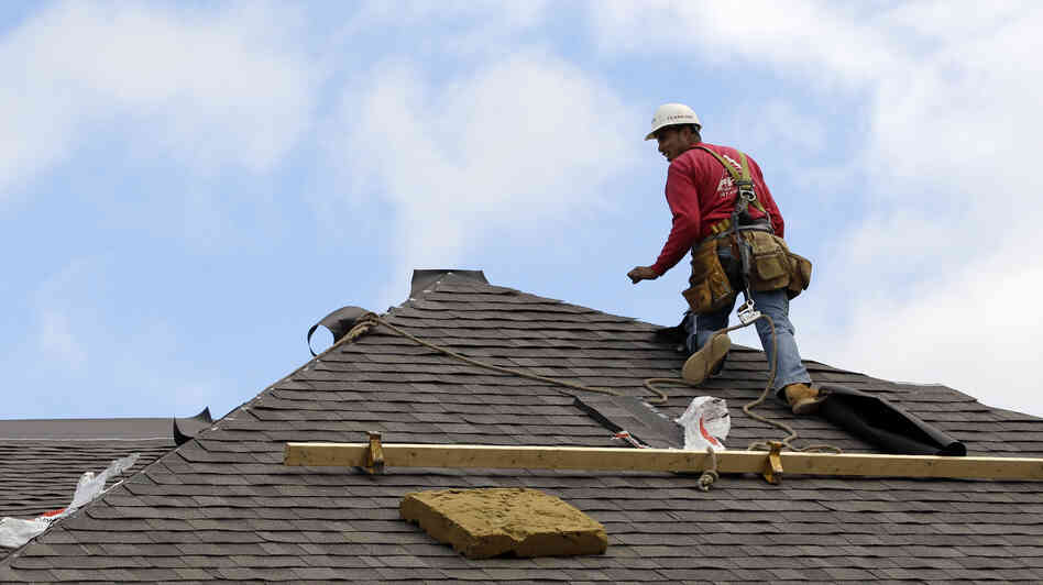 A construction worker finishes a roof in Ch