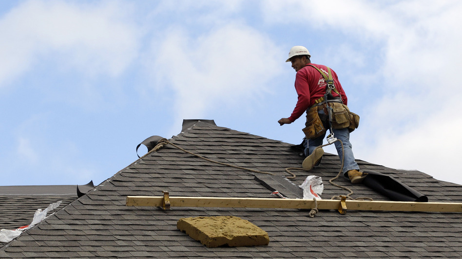 A construction worker finishes a roof in Chicago on Oct. 12. Signs of recovery in the housing market are springing up nationwide, but there's still a ways to go. (AP)