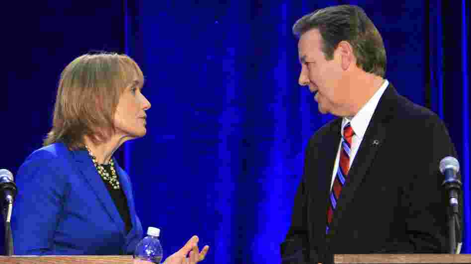 Democrat Maggie Hassan and Republican Ovide Lamontagne talk during a break in their gubernatorial debate in Henniker, N.H., on Oct. 4.
