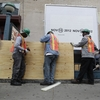 Workers cover an entrance with plywood at a subway station in New York City in preparation for flooding from Hurricane Sandy.
