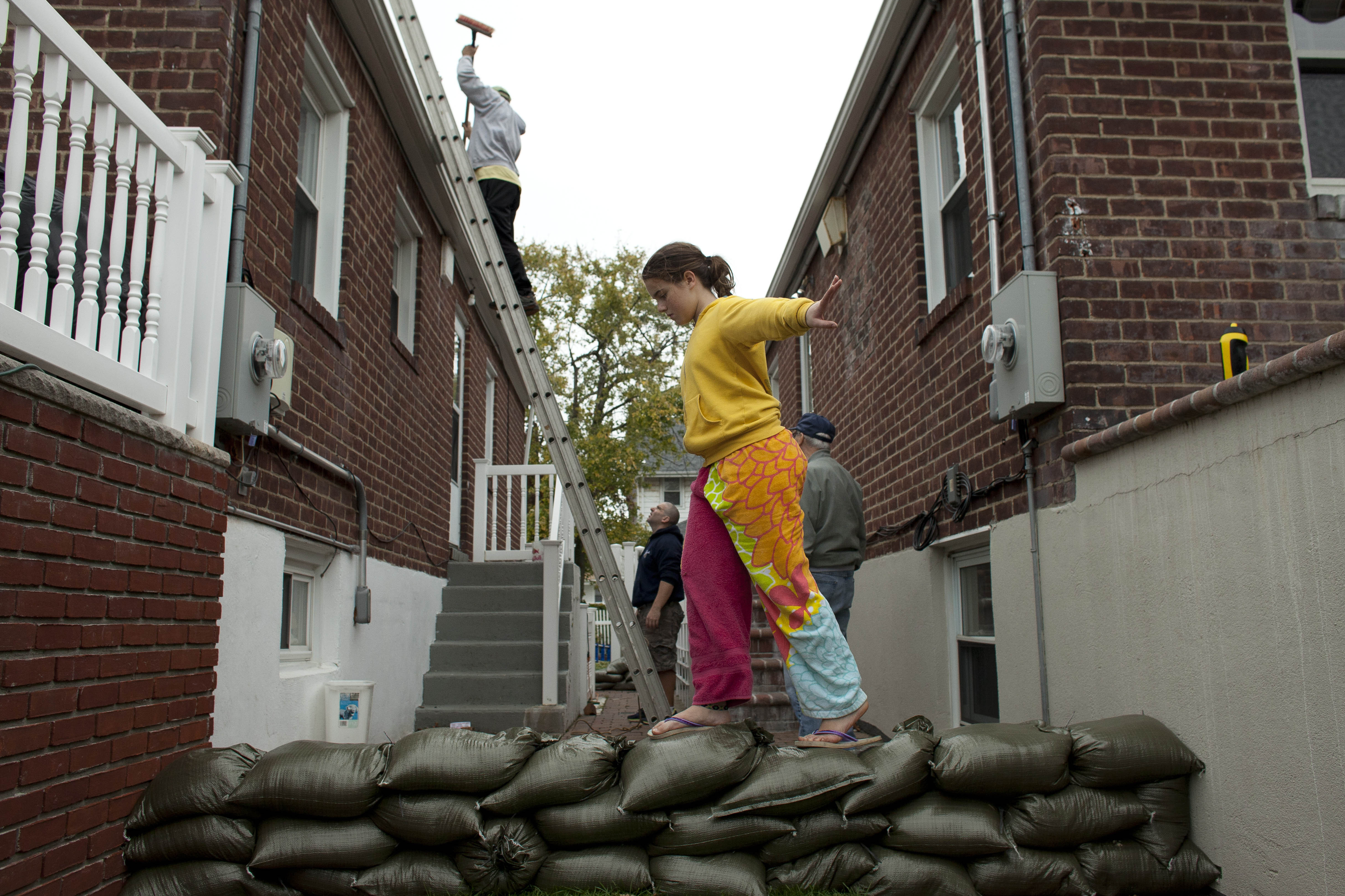 Bridget Donnelly walks on a sandbag wall outside her home in the Rockaway Beach neighborhood of Queens in New York City. Mayor Michael Bloomberg announced a mandatory evacuation of the city's low-lying coastal areas.