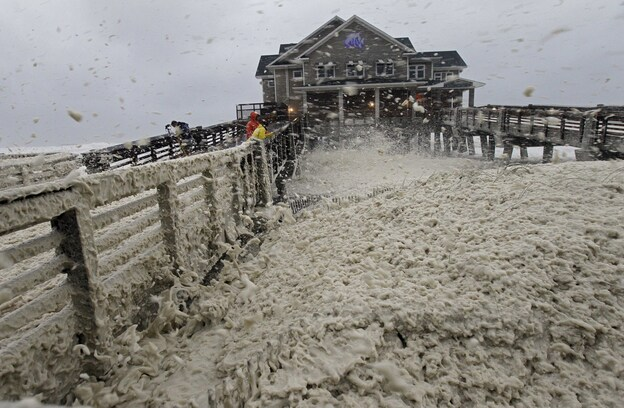 High winds blow sea foam onto Jennette's Pier in Nags Head, N.C., on Sunday, as wind and rain from Hurricane Sandy move into the area.