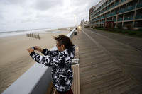 Mary Corrus takes a picture of the rough surf as Hurricane Sandy bears down on Ocean City, Md.