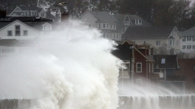 Waves crash over a road as Hurricane Sandy comes up the coast Monday in Winthrop, Mass. Economists are predicting the storm will cost tens of billions of dollars. (Getty Images)