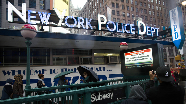 Pedestrians pass a New York Police Department station beside a closed subway entrance at Times Square on Monday. (AP)