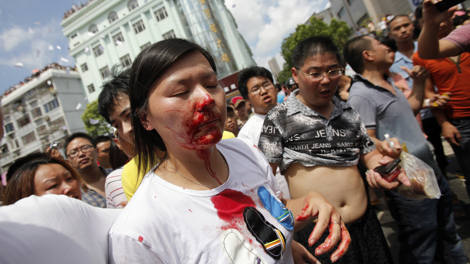 A bloodied woman is helped by demonstrators after clashes with police in a protest against an industrial waste pipeline in Qidong, Jiangsu province, on July 28. The Chinese government devotes enormous resources to suppressing dissent, but opposition to government policies is increasingly common. (Reuters/Landov)