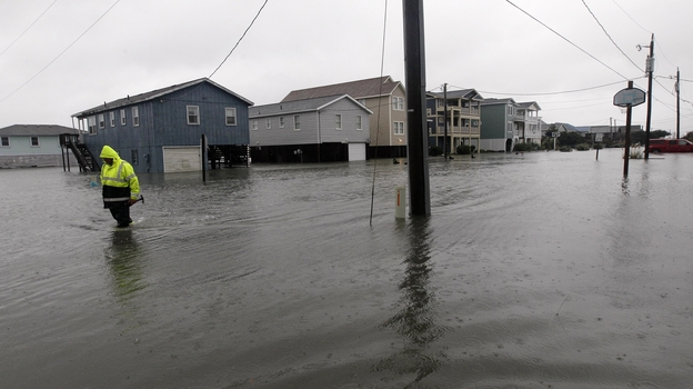 A Dare County utility worker checks on conditions along a flooded Ride Lane in Kitty Hawk, N.C., Monday, Oct. 29, 2012. (AP)