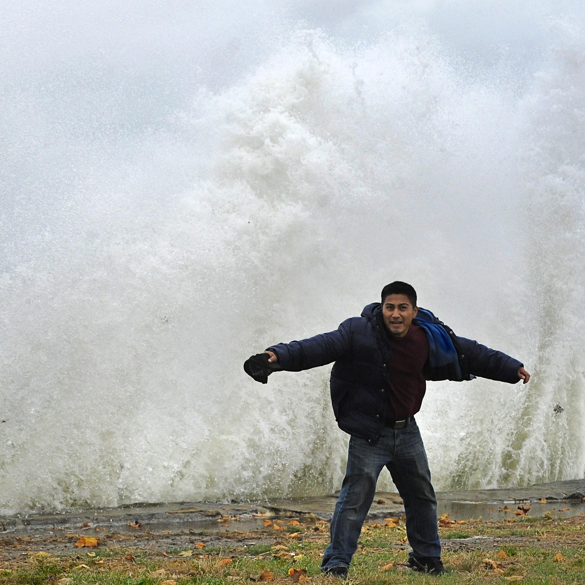 Hilavio Baquero stands in front of waves as winds from Hurricane Sandy reach Seaside Park in Bridgeport, Conn.