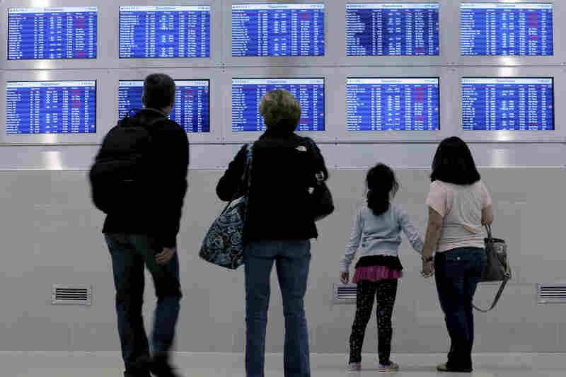 Travelers on Delta Airlines look at a departure screen in Detroit as dozens of departing flights have been canceled.