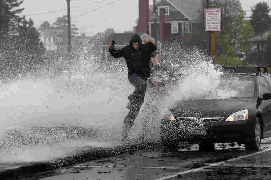 Caleb Lavoie (front) and Curtis Huard leap into the street as a large wave crashes over a seawall on the Atlantic Ocean in Kennebunk, Maine.