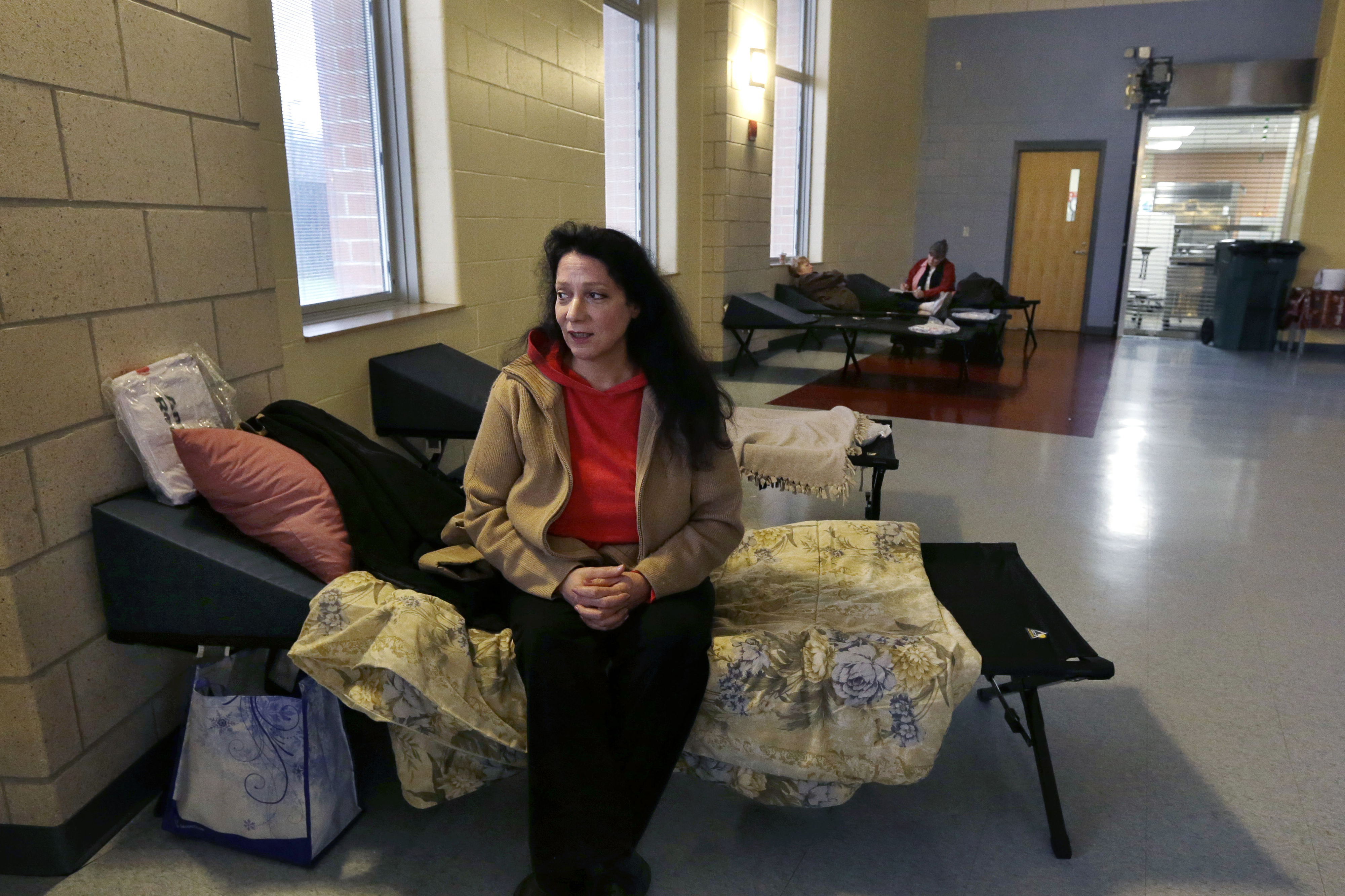 Diana Clarke sits on a cot set up by the Red Cross as she takes shelter from Hurricane Sandy at Weymouth High School in Weymouth, Mass.