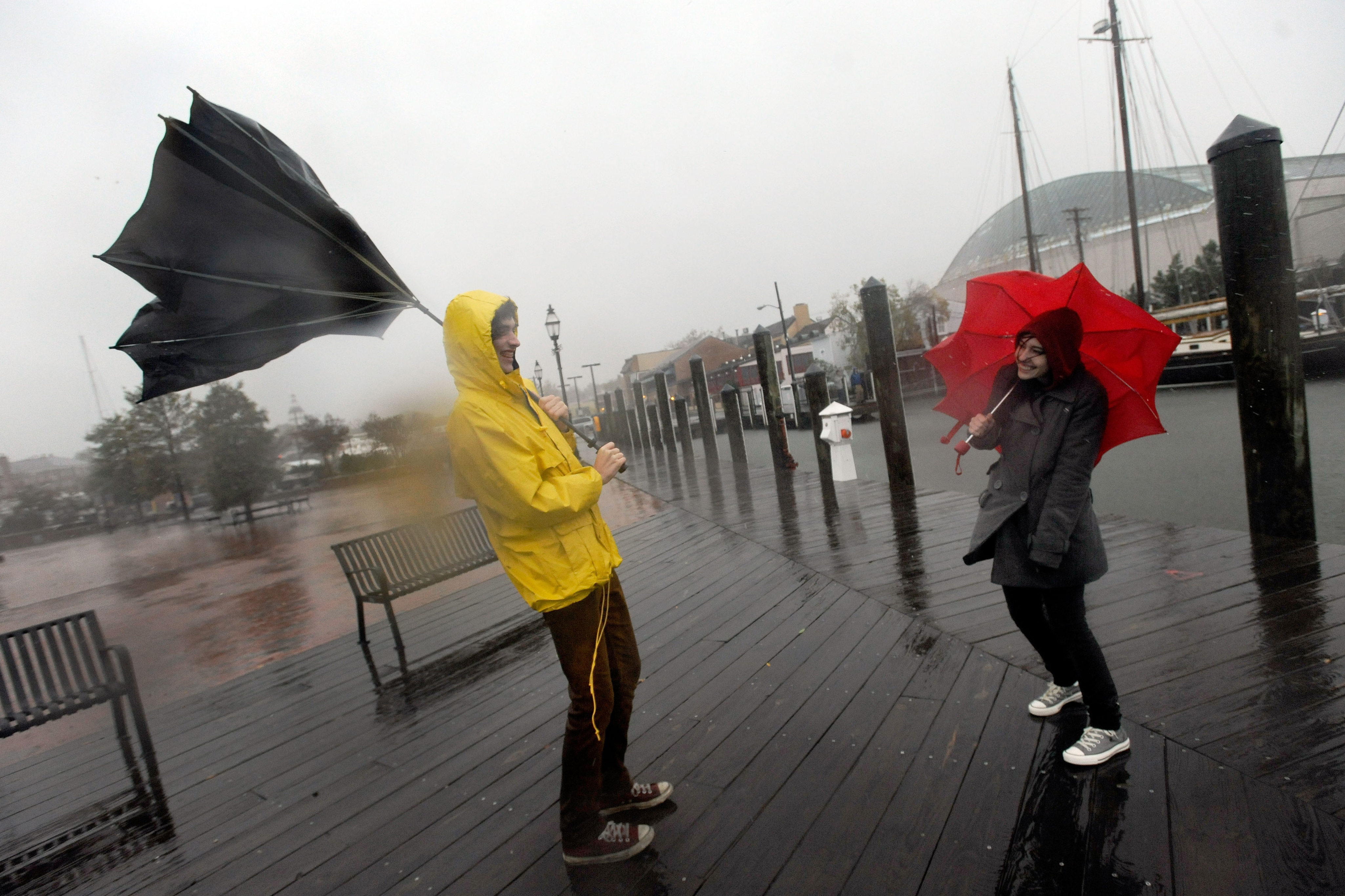 Jake Wilkerson (left) and Kaityln Baker struggle with their umbrellas as Hurricane Sandy approaches Annapolis, Md.