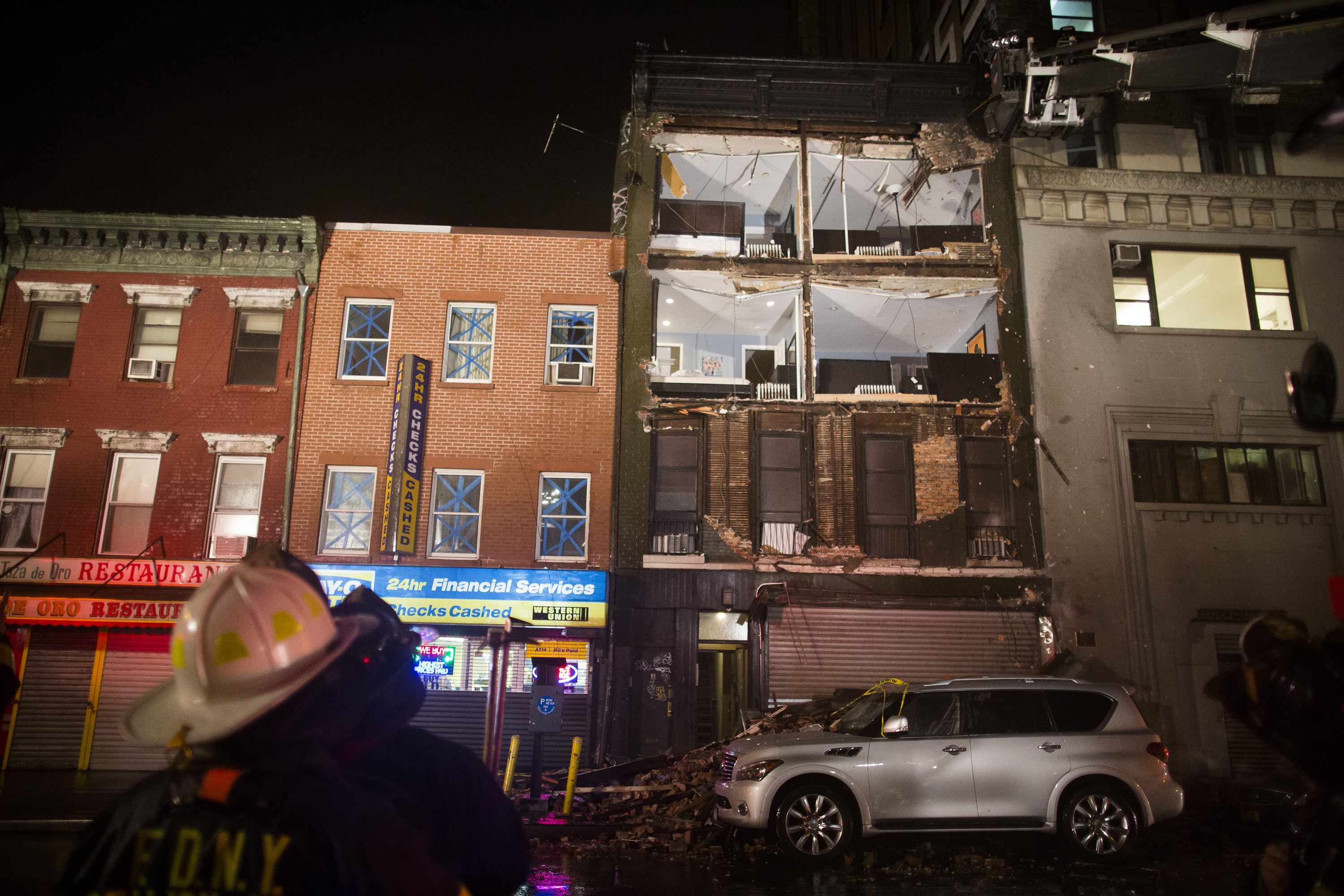 "Firefighters look up at the facade of a four-story building that collapsed onto the sidewalk in New York City. As of 7 p.m. ET Monday, Sandy had been reclassified as a ""post-tropical cyclone."""