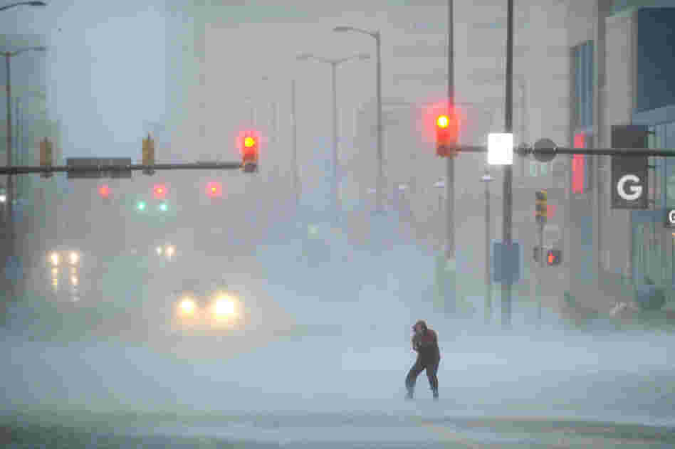 A journalist struggles to cross the street in Atlantic City. The city is like a ghost town, with casinos shuttered, tourists gone and many parts of the town inundated in knee-high water.