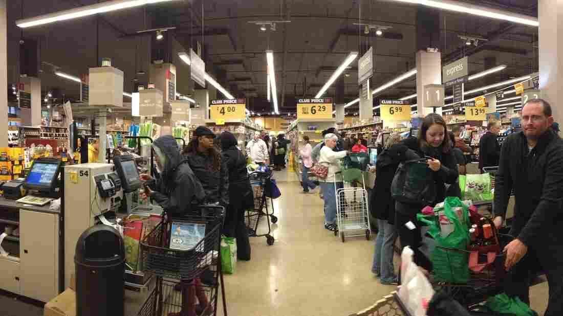 People wait to purchase groceries in self-checkout lanes at Sa