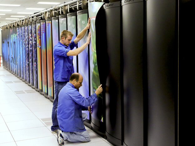 Cray employees put the finishing touches on Titan at the Department of Energy's Oak Ridge National Laboratory in Tennessee. The supercomputer may be the world's fastest. It's designed to do 20 petaflops — or 20,000 trillion calculations — each second. It consumes enough electricity to power a small city of 9,000 people.