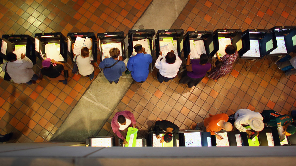 Early voters fill out ballots in Miami. Voting experts say Hurricane Sandy isn't likely to cause major disruptions — but that it would have been a far different matter had Florida taken a direct hit from the storm. (Getty Images)