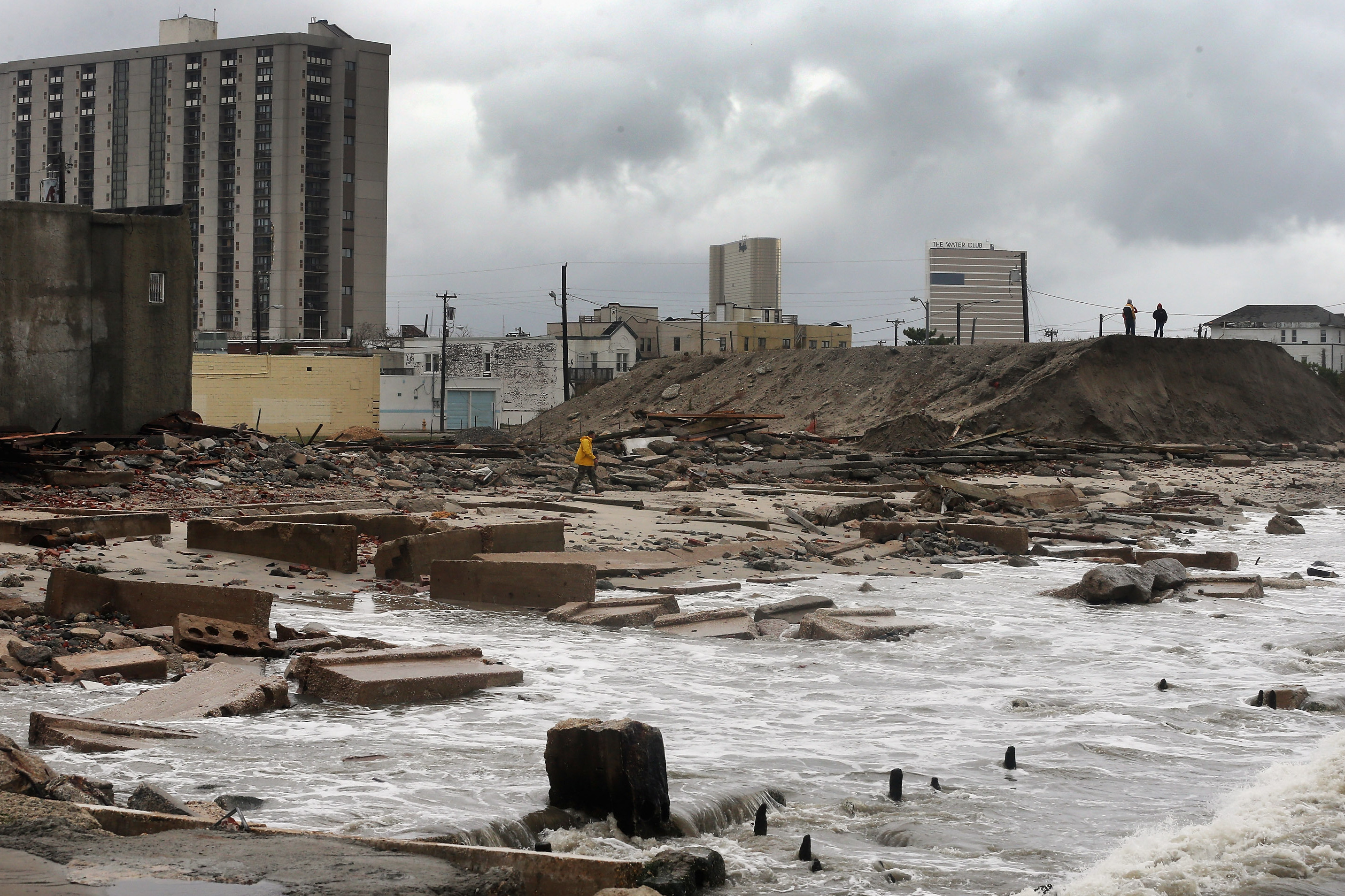 In Atlantic City, NJ, people stand on a mound of construction dirt to view the area where a 2,000-foot section of the 'uptown' boardwalk was destroyed by flooding from Hurricane Sandy. The storm has claimed more than 30 lives and has caused massive flooding across much of the Atlantic seaboard.