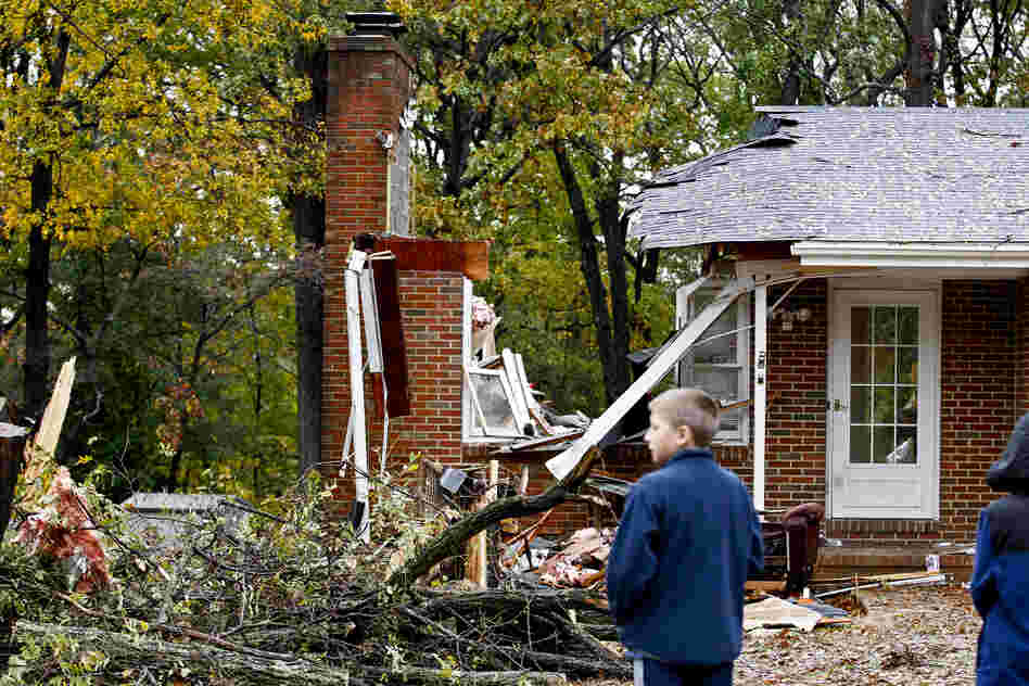 Reece Hiner, 11, looks at a destroyed home in Pasadena, Md., where the homeowner was killed overnight when a tree fell on his home during Sandy.