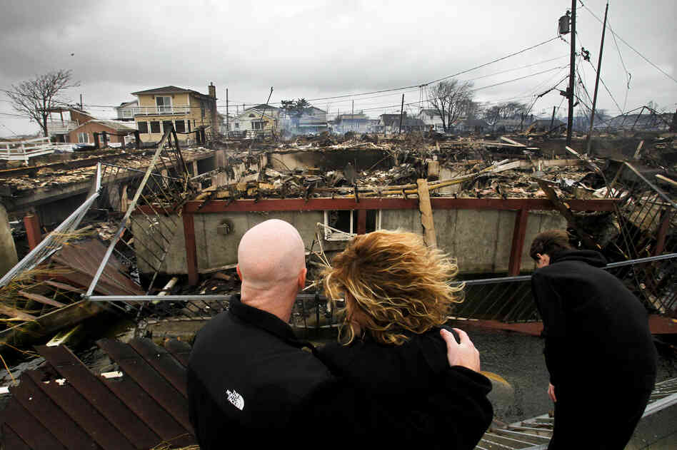 Robert Connolly, left, embraces his wife Laura as they survey the remains of her parent's home that burned to the ground in the Breezy Point section of Queens, N.Y. More than 50 homes were destroyed in the fire which swept through the oceanfront community during Superstorm Sandy. At right is their son, Kyle.