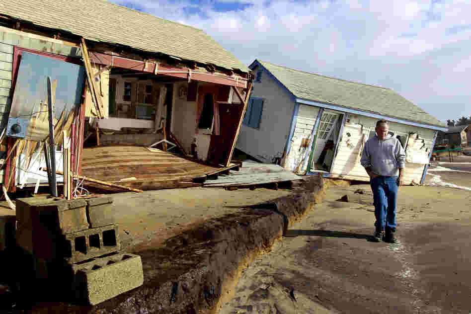 A man walks past cottages damaged by Sandy on Roy Carpenter's Beach in the village of Matunuck, in South Kingstown, R.I.