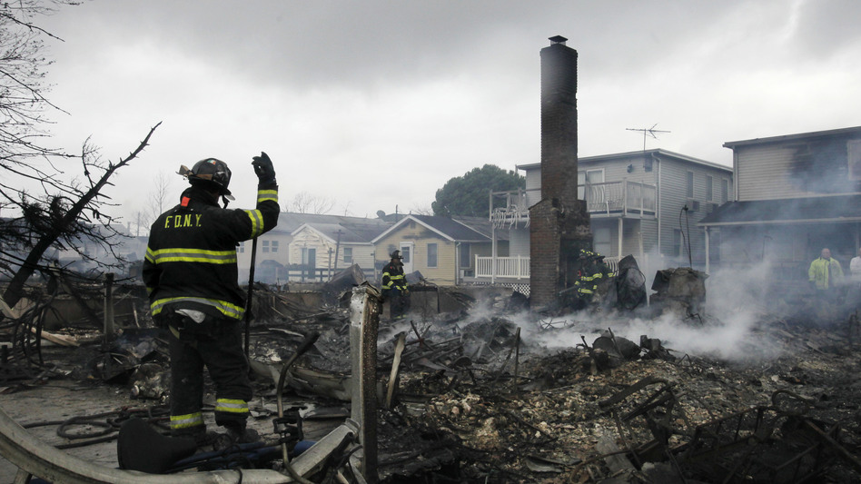 A firefighter surveys the smoldering ruins of a house in the Breezy Point section of New York. (AP)