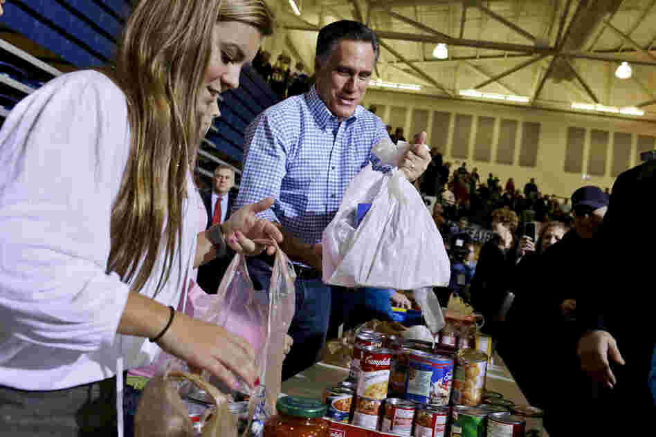 Republican presidential candidate Mitt Romney holds bags of food as he participates in a campaign event collecting supplies for victims of Sandy at the James S. Trent Arena in Kettering, Ohio.