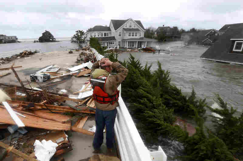 Brian Hajeski, 41, of Brick, N.J., reacts as he looks at debris of a home that washed up on to the Mantoloking Bridge in Mantoloking, N.J. Storm damage has halted mass transit and cut power to more than 6 million homes and businesses.
