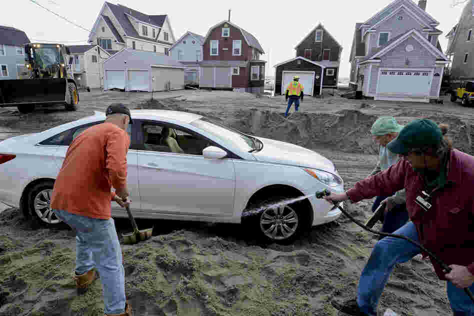People work to free a car stuck in beach sand deposited during high tide in Milford, Conn.