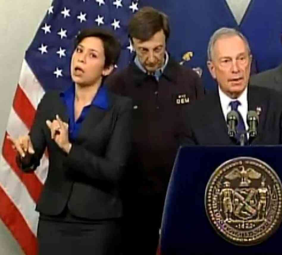 Fans like her style: Mayor Michael Bloomberg (at right) briefing New Yorkers about Hurricane Sandy on Monday. At left is his sign language interpreter, who the mayor identified as