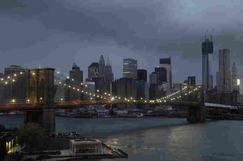 The lights on the Brooklyn Bridge stand in contrast to the lower Manhattan skyline which has lost its electrical supply following Superstorm Sandy on Tuesday.