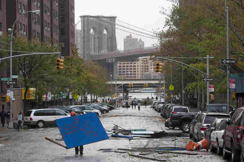 A worker picks up plywood from a scaffolding site in New York's Lower East Side in the aftermath of Sandy on Tuesday.