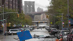 A worker picks up fallen plywood from a scaffolding site in the Lower East Side during a clean up in the aftermath of Sandy in New York City on Tuesday.