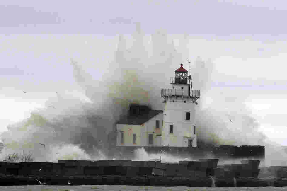 Waves pound a lighthouse on the shores of Lake Erie, near Cleveland. High winds spinning off the edge of Sandy took a vicious swipe at northeast Ohio, uprooting trees, cutting power to hundreds of thousands, forcing school closures and flooding parts of major commuter arteries that run along the lake.
