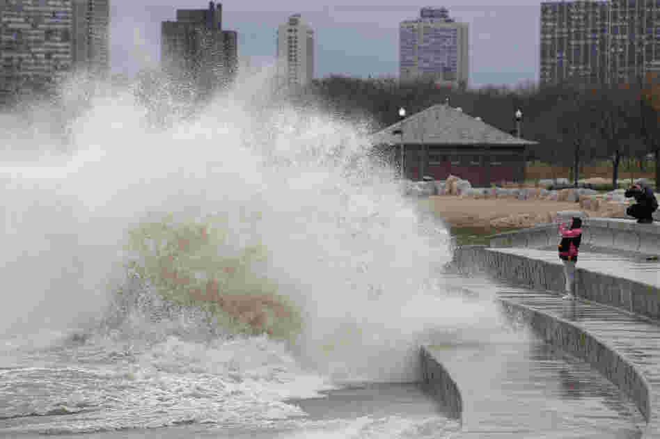 Onlookers take photos as strong waves created by Sandy crash against the Lake Michigan waterfront on the South Side of Chicago, Ill.