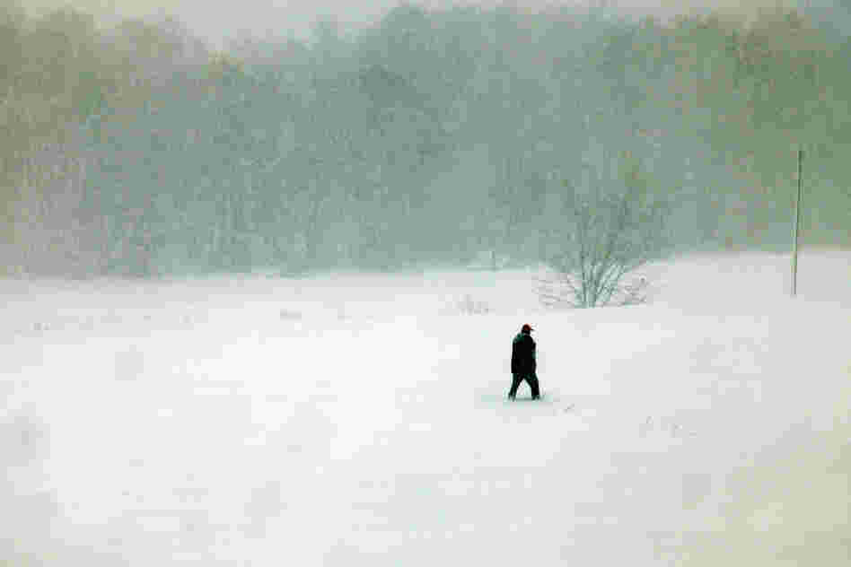 A person walks through snow in Belington, W.Va. Sandy buried parts of the state under more than a foot of snow, cutting power to at least 264,000 customers. Authorities closed nearly 50 miles of interstate.