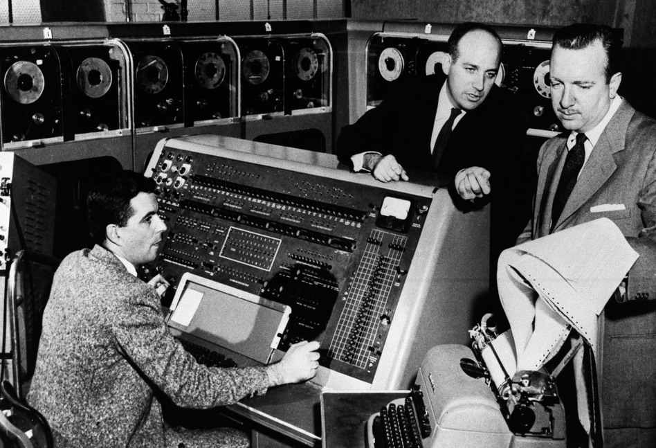 Walter Cronkite (right) listens as Dr. J. Presper Eckert (center) describes the functions of the UNIVAC I computer he helped develop in the early 1950s. (AP)