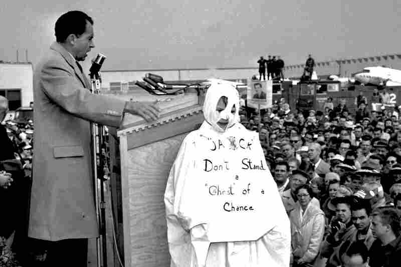 """Richard Nixon addresses a crowd while campaigning for president against John F. Kennedy in 1960. To his right is 10-year-old Tom Lemke, in a ghost costume that reads """"Jack Don't Stand a Ghost of a Chance,"""" referring to Kennedy. Nixon called attention to the boy when he saw him in the crowd. So, moral of the story: Wearing a costume can make you famous."""