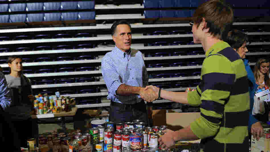 Mitt Romney helps collect and pack donated goods for those affected by Hurricane Sandy, in Kettering, Ohio, on Tuesday.