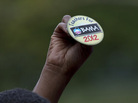 An attendee holds up a button at a speech by President Obama on Sept. 17 in Cincinnati.