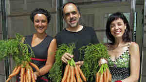 At the Bescanó municipal theater in northeastern Spain, director Quim Marcé (center) and actresses Meritxell Yanes (left) and Elena Martinell (right) display carrots for sale.