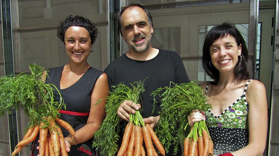 At the Bescanó municipal theater in northeastern Spain, director Quim Marcé (center) and actresses Meritxell Yanes (left) and Elena Martinell (right) display carrots for sale. (Quim Marcé)