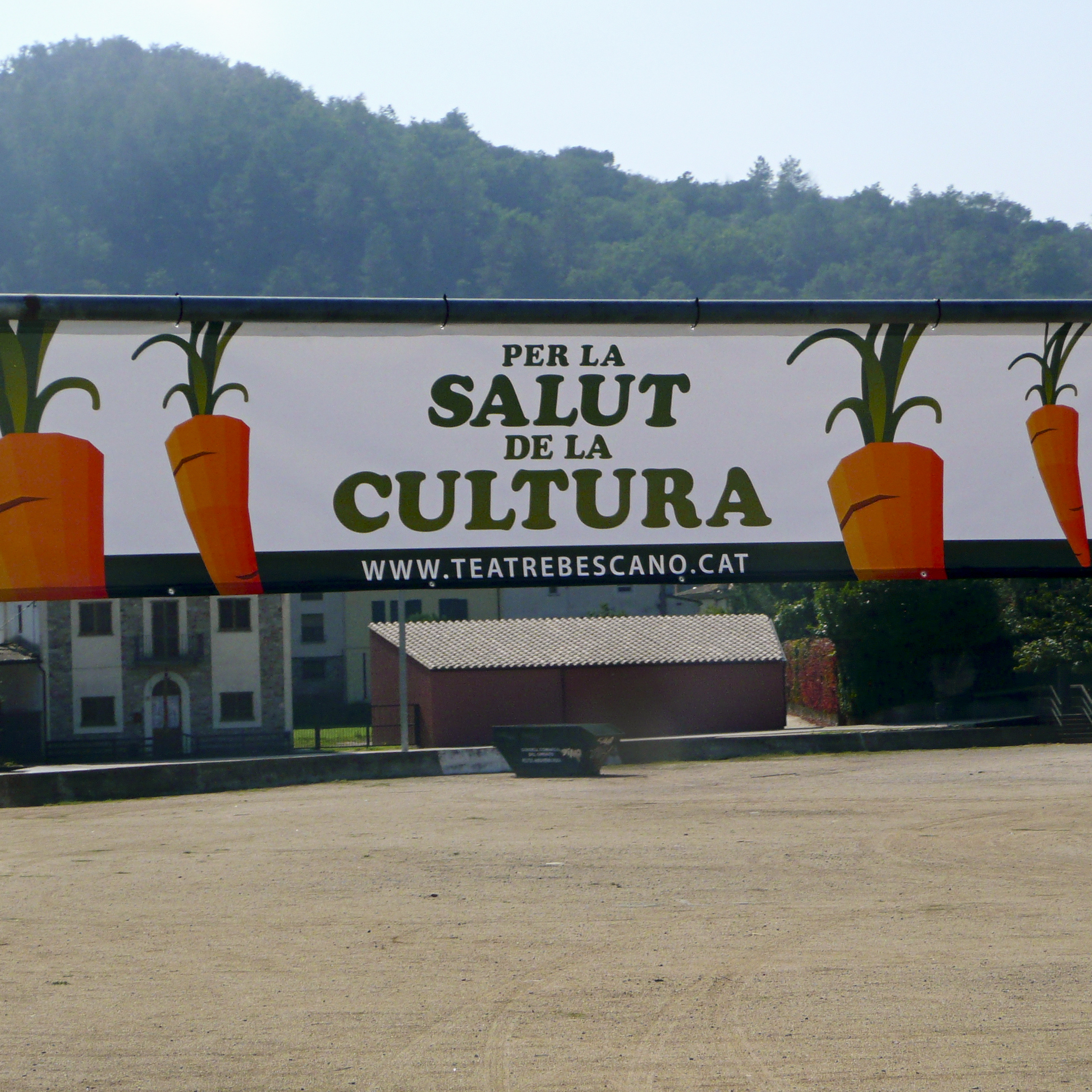 "Banners at the entrance to the village of Bescanó announce the local theater's carrot-selling campaign, with the slogan ""For the Health of Culture,"" in Catalan language."