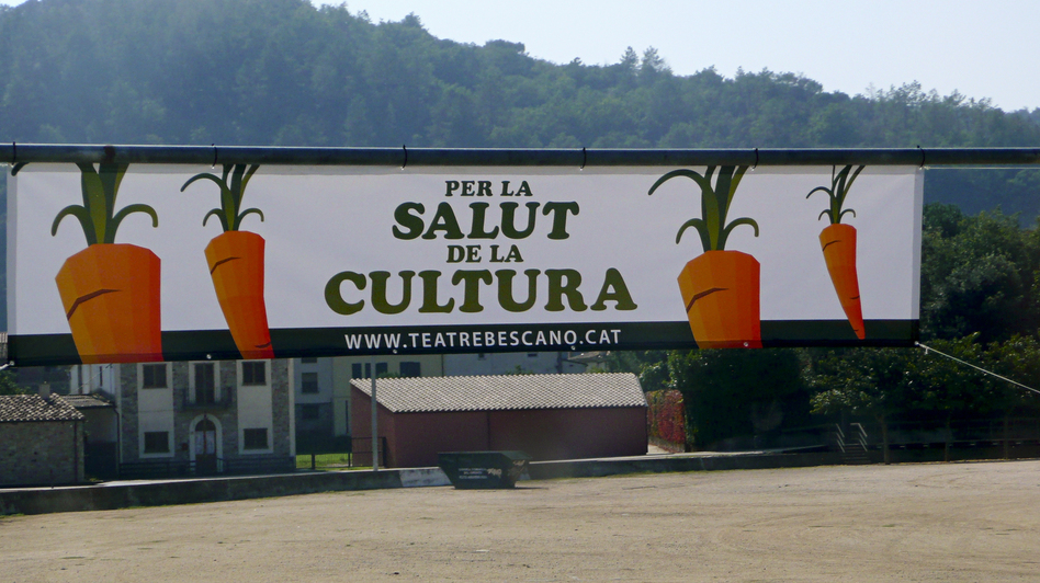 "Banners at the entrance to the village of Bescanó announce the local theater's carrot-selling campaign, with the slogan ""For the Health of Culture,"" in Catalan language. (NPR)"