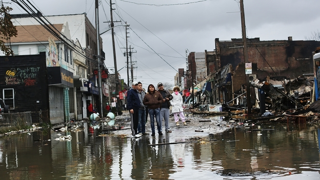 People look at homes and businesses destroyed during Superstorm Sandy on Tuesday in the Rockaway section of Queens, N.Y. (Getty Images)