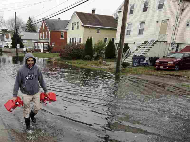 Christian Codorniu carries gas containers Tuesday to fill a home generator following the superstorm in Little Ferry, N.J.