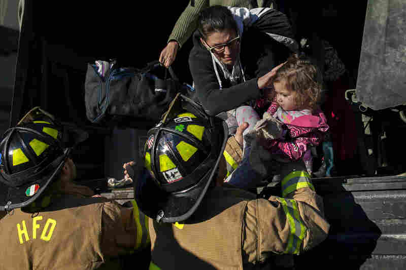 Hoboken firefighters bring Ali LaPointe and her daughter, Eliza Skye, from a National Guard truck after being moved from their home in Hoboken. Parts of the city are flooded.
